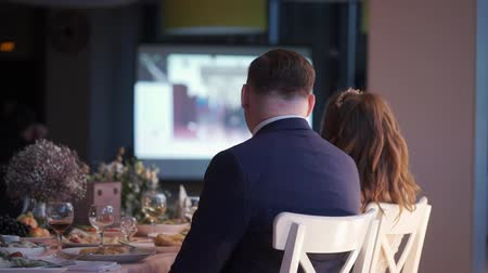 watch tv : Bride and groom watching video on projector at the wedding party reception and have fun