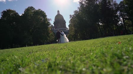 st isaac's cathedral : Bride and groom walking in park at the city Stock Footage