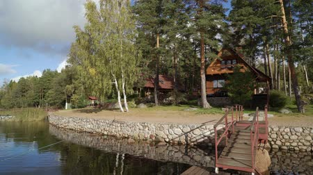 jezero : A wooden cottage near lake or sea. Luxury house for vacations. Summer day