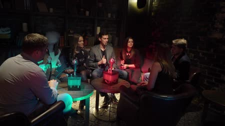 lélegzet : Hookah smoker. Group of young man, woman and couples smoking shisha or hookah in cafe or bar. Resting in shishabar lounge.