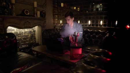 tabaco : Hookah smoker. Young man smoking shisha or hookah in cafe or bar. Resting in shishabar lounge. Businessman working with laptop