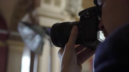 mirrorless : Professional photo shooting indoors. Photographer is taking pictures photos with a digital camera DSLR. Photosession Stock Footage