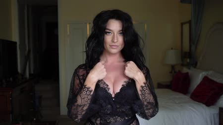 seio : Young sexy brunette woman in lingerie staying in bedroom near window and posing. Flirting of lovely female in hotel room. Slowmotion. Touching herself big breast in black bra. Plastic surgery and implants.
