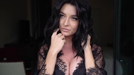 болваны : Young sexy brunette woman in lingerie staying in bedroom near window and posing. Flirting of lovely female in hotel room. Slowmotion. Touching herself big breast in black bra. Plastic surgery and implants.