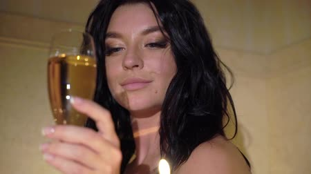 üstsüz : Young sexy brunette woman going to bathroom, undressing removing bathrobe and laying in bathtube with candles. Romantic dating. Slowmotion. Girl drinking champagne form a glass.