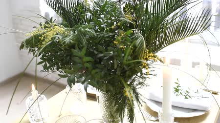 exotic dishes : Beautiful table decoration with exotic bouquet of leaves and mimosa flowers, home party table setting