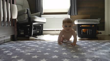 happy little baby boy crawling on floor at home