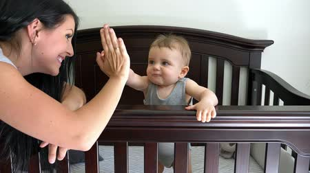 Mother putting baby to sleep at the crib doing high five
