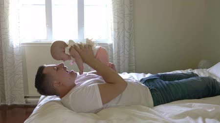 Portrait of father with her 3 month old baby in bedroom Стоковые видеозаписи
