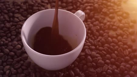 Pouring coffee surrounded by coffee beans in slow motion