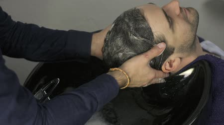 şampuan : Man washing hair with shampoo in salon Stok Video