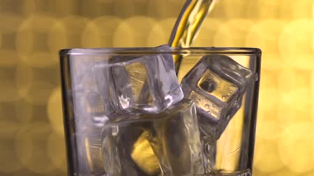 whisky : glass with ice cubes and pouring whiskey