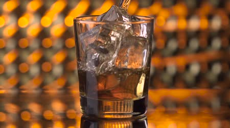 whisky : Pouring whiskey into glass with ice cubes