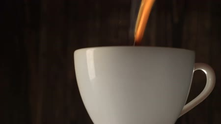 xícara de café : Pour coffee into white cup with steam on b;ack background.