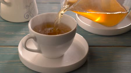 black tea : Glass teapot pouring green tea into cup on wooden table Stock Footage