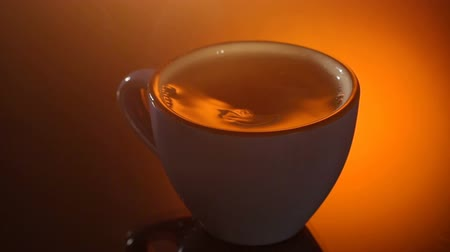 hot beverage : Cup of hot tea with steam on shiny background.