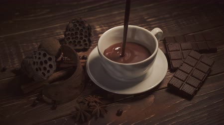 hot beverage : pouring hot chocolate with anise and cinnamon sticks on dark wooden table