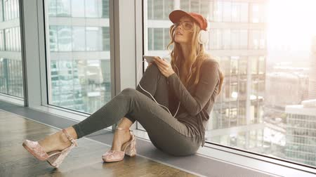 izgatott : Pretty smiling girl sitting by window listening to music with headphones using mobile