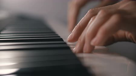 teclado : Woman hand playing a MIDI controller keyboard synthesizer close up.