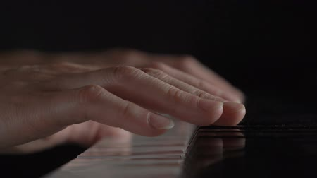 piano parts : Hands of a woman playing the piano on black background Stock Footage