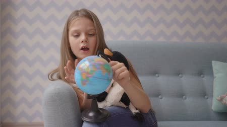 six worlds : Cute girl holding and rotate a small globe while sitting on sofa at home