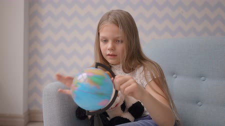 six worlds : Cute little girl holding and rotate a small globe while sitting on sofa