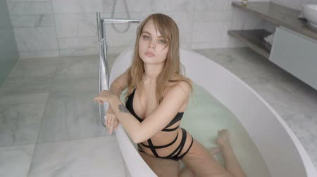 toalhas : Young girl in a black sexy swimsuit takes a bath