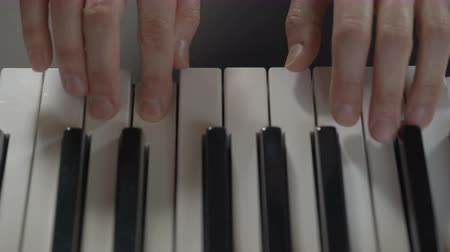 piano parts : Hands of a woman playing the piano on black background, top view, closeup Stock Footage