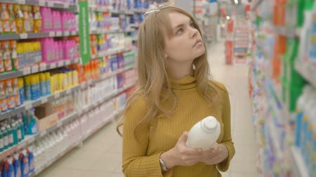 corredor : Beautiful young woman is choosing household products while doing shopping at the supermarket Vídeos