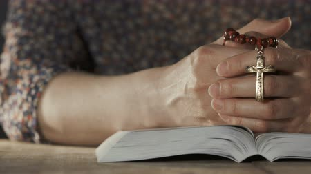 evangelical : Woman praying with her bible on wooden table