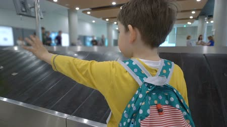 reclaim : Liittle boy waiting for his luggage at conveyor belt in arrivals lounge of airport terminal building