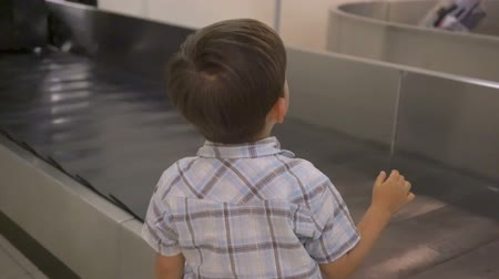 reclaim : Little boy waiting for suitcase on luggage conveyor belt in the baggage claim at airport