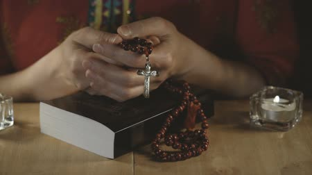 jehovah witness : Womens hands holding a cross with rosary on a closed bible.
