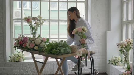 flower shops : Young florist girl counting bouquet cost using tablet at her flower studio