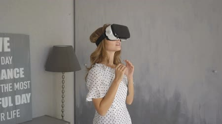 vr headset : Excited woman interacting with her virtual environment with her mouth open as she tries out VR goggles Stock Footage
