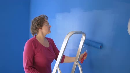 obnova : Woman doing wall painting with blue paint standing on the ladder
