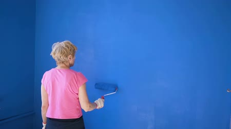 decorador : Old woman painting interior wall with paint roller in new house with blue paint