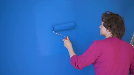 renovar : Woman doing wall painting with blue paint standing on the ladder