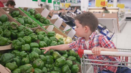healthyfood : little boy in supermarket choosing bulgarian peppers sitting in the trolley. Shopping in store, fresh products for kitchen and cooking.