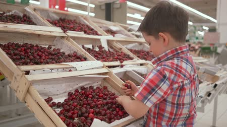 bazar : Funny little boy picking cherry from the box during family shopping in hypermarket