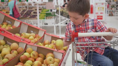 brzoskwinia : Funny little boy picking apple from the box sitting in the trolley, during family shopping in hypermarket