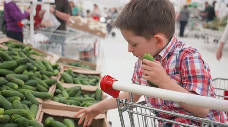 cereal product : Cute little boy choosing fresh cucumbers in supermarket. Stock Footage
