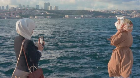 hoşgörü : Two muslim woman making photos against the backdrop of the Istambul city