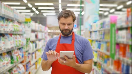 sabão : Handsome salesman using digital tablet standing among shelves In supermarket