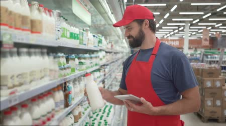scaffale supermercato : Handsome male merchandiser checking milk products with digital tablet