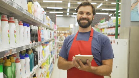 deterjan : Handsome smiling supermarket employee with pc tablet standing among shelves
