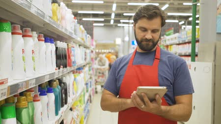 liste : Store supervisor with tablet pc in hand checking the quality of the product in supermarke