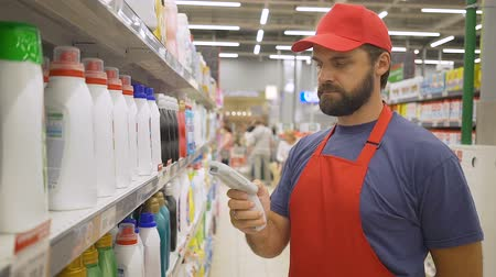 deterjan : supermarket employee in red uniform scanning product barcode in modern retail store Stok Video