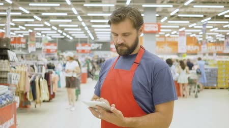 tezgâhtar : Handsome supermarket clerk using a touch screen tablet in supermarket