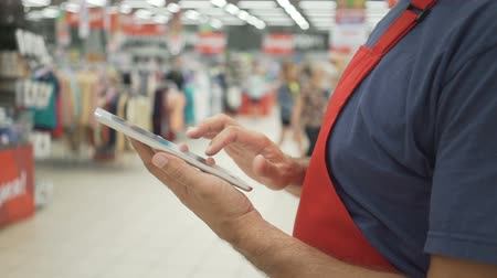 scaffale supermercato : Sales clerk in red apron using a digital tablet with store on background Filmati Stock